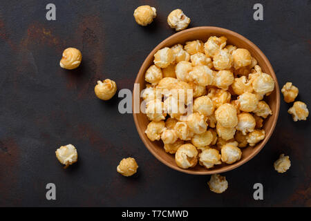 Caramel popcorn in bowl on dark table background top view