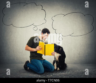 Funny border collie and his master reading together an interesting book. Dog owner down on knees training his cute puppy over grey wall room with blan - Stock Photo