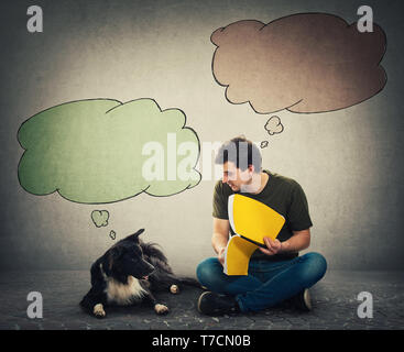 Curious purebred border collie dog and his master reading together an interesting book. Owner seated on floor training his cute puppy and colorful bla - Stock Photo