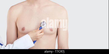 Doctor with stethoscope checking patient heart beat on gray background. - Stock Photo