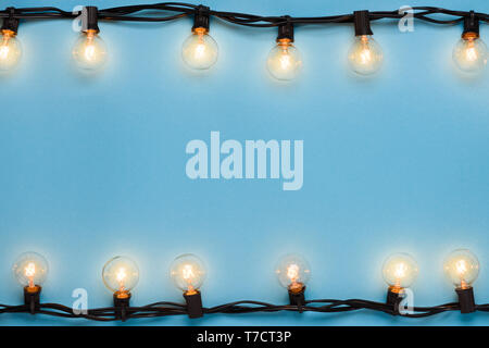 Garlands of lamps warm light edison lights on blue background with space for text - Stock Photo