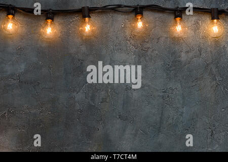 Garland of warm glowing edison glass lamps on rustic wall border - Stock Photo