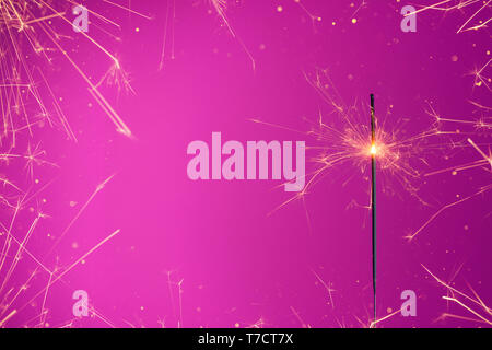 Burning sparkler bengal fire in frame of sparkles and gold glitter. - Stock Photo