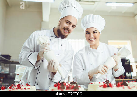 Confectioners with a bag for the cream will decorate the cake. - Stock Photo