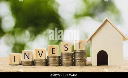Property investment, home loan, house mortgage ,real estate financial concept. Money coin stack growing with wooden residential house model. Depicts a - Stock Photo