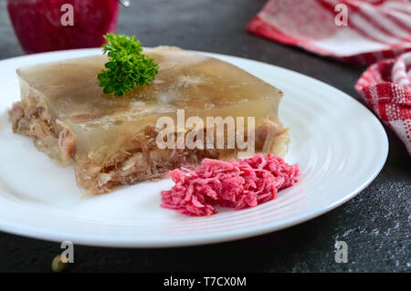 Meat jelly with spicy horseradish on a white plate on a black background. Slavonic traditional cold dish. Close-up - Stock Photo