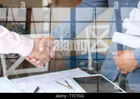 engineer handshaking. architect shaking hands for successful deal in building construction project. teamwork cooperation double exposure with crane - Stock Photo
