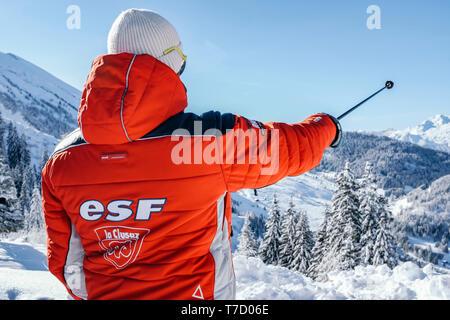 French ski school ESF ski instructor, ski resort of La Clusaz (central-eastern France). Ski instructor pointing out a direction with a ski pole - Stock Photo