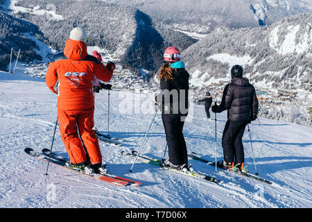 French ski school ESF ski instructor, ski resort of La Clusaz (central-eastern France). Ski instructor and learners atop a ski run and view over La Cl - Stock Photo