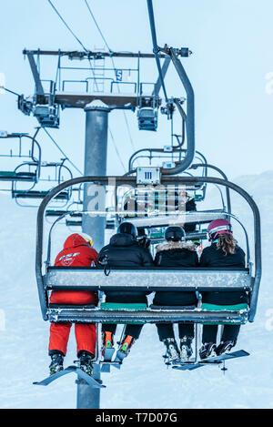 French ski school ESF ski instructor, ski resort of La Clusaz (central-eastern France). Ski instructor and learners sitting on a chairlift - Stock Photo
