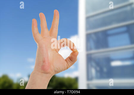 Closeup of man showing okay gesture with fingers in front of building made out of glass - Stock Photo