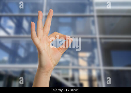Woman having glass building as background showing fine gesture with fingers closeup - Stock Photo