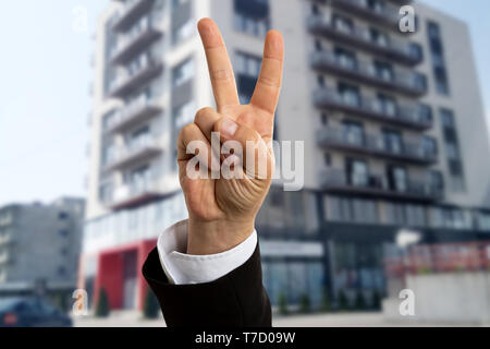 Male real estate agent showing victory or peace sign in front of apartment building for rent closeup - Stock Photo