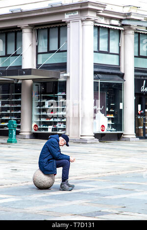 Sad lonely man sitting on a ball in a city - Stock Photo