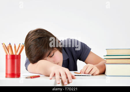 Tired and overworked caucasian teenager pupil felt asleep at the desk while doing his homework. Concept of hard educational process - Stock Photo