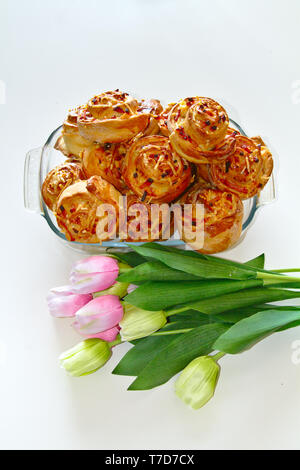 Worlds best pinwheels with delicious ham and cheese. Surrounded with pink and white tulips. - Stock Photo