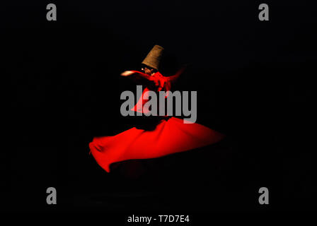 Whirling dervish on black background in red costume - Stock Photo