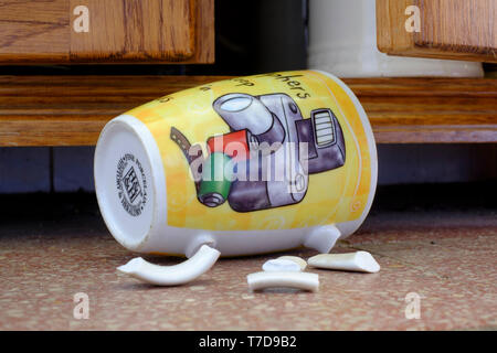 photographers coffee mug laying on tiled floor with broken handle after falling out of cupboard concept lack of focus - Stock Photo