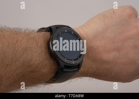 male hand wearing smart watch with blank screen on gray background - Stock Photo