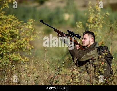 Hunting and trapping seasons. Bearded serious hunter spend leisure hunting. Hunter hold rifle. Man wear camouflage clothes nature background. Hunting permit. Hunting is brutal masculine hobby. - Stock Photo