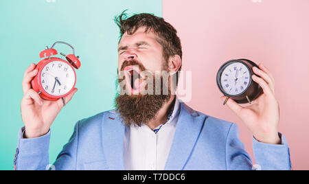 Guy unshaven puzzled face having problems with changing time. Time zone. Changing time zones affect health. Does changing clock mess with your health. Man bearded hipster hold two different clocks. - Stock Photo