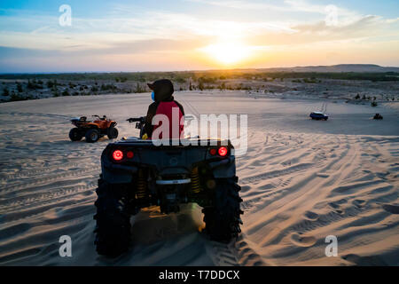 Young man in safari trip through egyptian desert driving ATV at sunset. Quad bikes safari in the desert near Hurghada, Egypt Stock Photo
