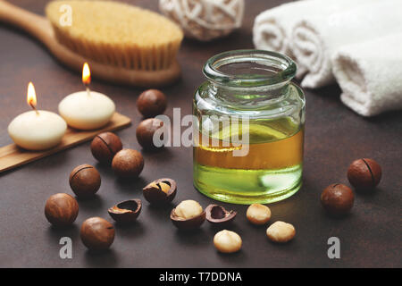 macadamia oil in a glass bottle, macadamia nuts, objects for spa on a brown background - Stock Photo