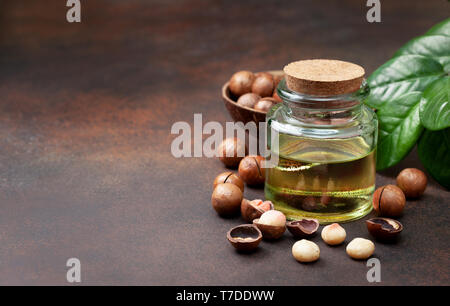macadamia oil in a glass bottle, macadamia nuts on a brown background - Stock Photo