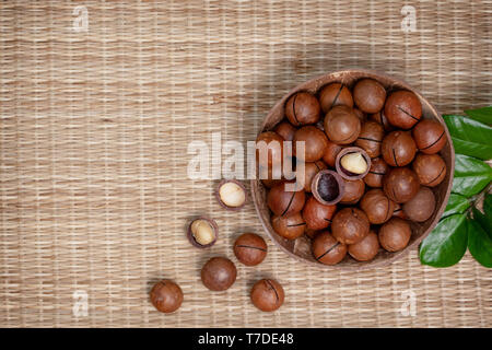 macadamia nuts in the bowl on straw (bamboo) background. view from above