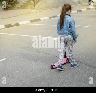 Little girl in a denim jacket walks down the street to ride scooter - Stock Photo