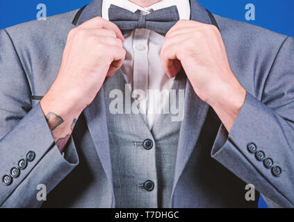 Man adjust suit with bow tie. Formal suit jacket close up. Male fashion and aesthetic. Businessman formal outfit. Classic style aesthetic. Perfect suit fit him. Menswear shop. Hands fixing bow tie. - Stock Photo
