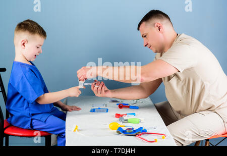 Man doctor sit table medical tools examining little boy patient. Pediatrician concept. Health care. Child care. Careful pediatrician check health of kid. Medical examination. Medical service. - Stock Photo