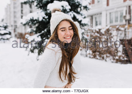 Portrait joyful young woman with long brunette hair having fun on street full with snow. Knitted hat, white woolen sweater, amazing smile, closed eyes, enjoying winter time - Stock Photo