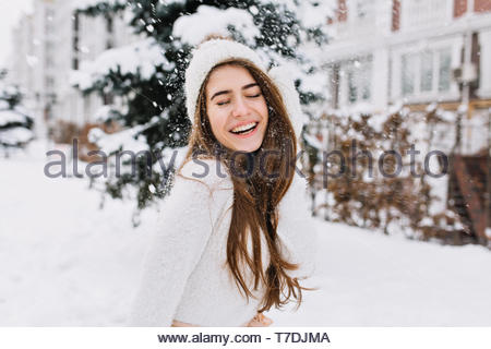Happy winter moments of joyful young woman with long brunette hair, white winter clothes having fun on street in snowing time. Expressing positivity, true brightful emotions, smiling with closed eyes - Stock Photo