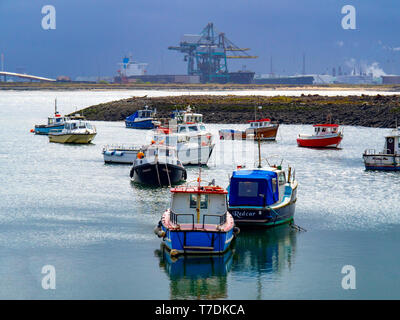 Fishing and pleasure boats in Paddys Hole Harbour, Teesmouth, Redcar Cleveland UK, with a bulk carrier ship at the Redcar Bulk Terminal - Stock Photo