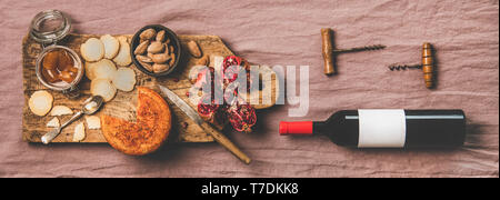 Wine and snack set. Flat-lay of wine bottle with blank label, vintage corkscrews and cheese and appetizers board over dusty pink linen table cloth, to - Stock Photo