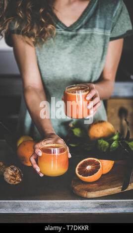 Young female holding two glasses of freshly squeezed blood orange juice or smoothie in hands near concrete kitchen counter. Healthy lifestyle, vegan,  - Stock Photo