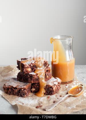 Chocolate and Macadamia Nut Brownies with Salted Caramel Sauce - Stock Photo