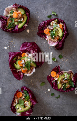 Healthy eatable radicchio bowls with couscous , avocado, dates. carrots, cucumber, herbs and sesame seeds over grey concrete background - Stock Photo