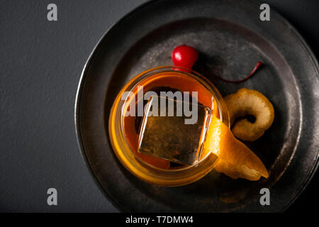 Old fashioned cocktail with large orange peel and artisan ice cube on a dark metal platter with cherry garnish. - Stock Photo