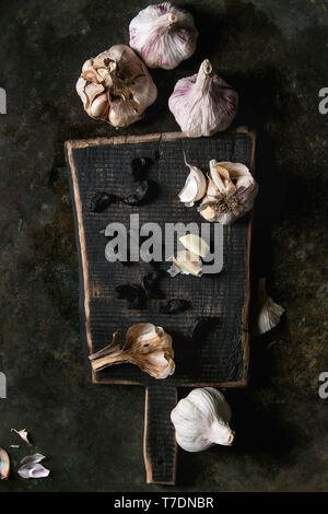 Variety of fresh organic garlic bulbs whole and peeled and cloves of black fermented garlic on wooden chopping board over dark metal background. Flat