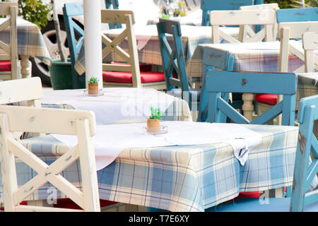 Tables and chairs in a typical traditional  Mediterranean restaurant on terrace in light blue and white color with plaid tablecloth, detail - Stock Photo