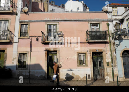 Old man carrying hessian sack and food bag walking past a house on a street in the Alfama district of Lisbon Portugal Europe EU  KATHY DEWITT - Stock Photo