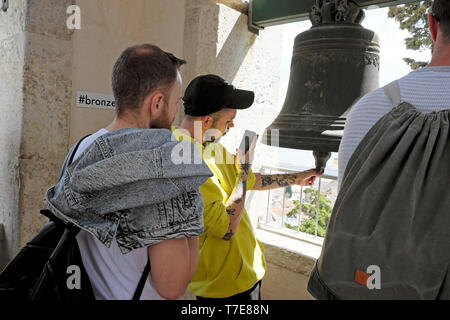 Young man tourist records the sound of bell with iphone in tower of Torre da Igreja do Castelo de São Jorge Lisbon Portugal Europe EU KATHY DEWITT - Stock Photo