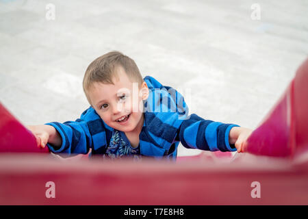 Little cheeky mischevious Caucasian boy climbing up the red plastic outdoor slide on a playground - Stock Photo