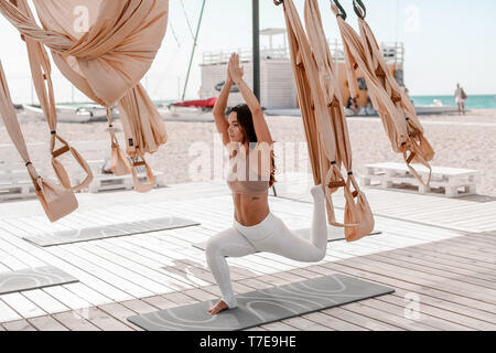 Beautiful woman engaged in antigravity yoga outdoors by the sea on the beach. - Stock Photo