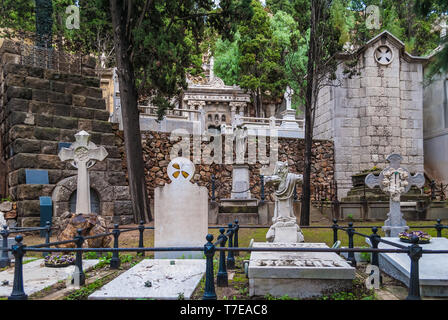 Several graves and crypts with gravestones, crosses and sculptures on the Montjuic Cemetery, Barcelona, Catalonia, Spain - Stock Photo