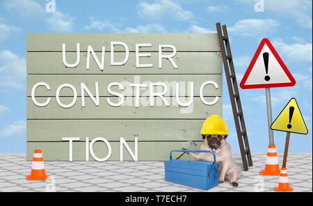 cute repairman pug puppy dog with yellow safety helmet, sitting down next to wooden board sign, with text under construction - Stock Photo