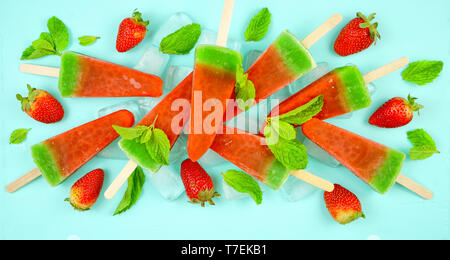 Watermelon flavored summer theme ice cream popsicles on pink and blue background. - Stock Photo