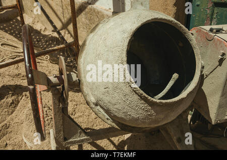Old cement mixer and sand in a construction site of a house at Castelo de Vide. Nice town with medieval castle at the Portugal eastern border. - Stock Photo